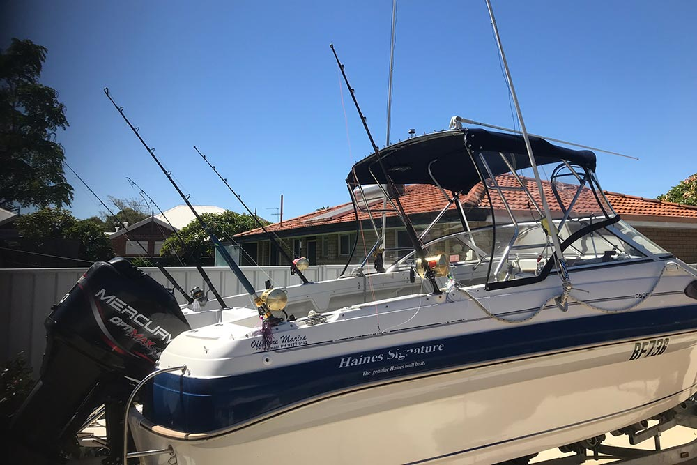 Picture of a Haines Signature fiberglass boat with a black Mercury motor rigged up and prepped for a great day of fishing.