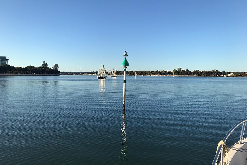 Green marine navigation marker on a calm bay